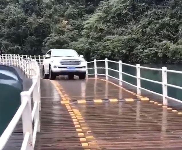 中国湖北省の水上に浮かぶ橋をたわませながら進む車
